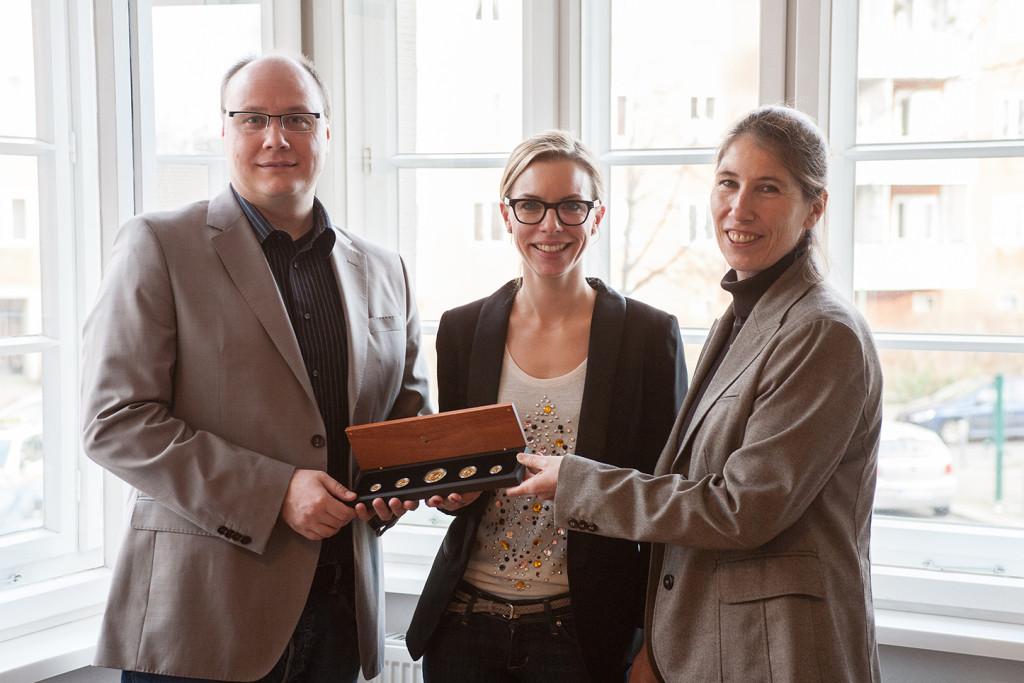 Anna Hettche-Stork (Mitte), Teamleiterin Inside Sales bei EBERTLANG, überreicht den glücklichen Gewinnern Michael Schröter (links) und Laetitia Coorssen (rechts), Pentacom GmbH, den Hauptpreis.