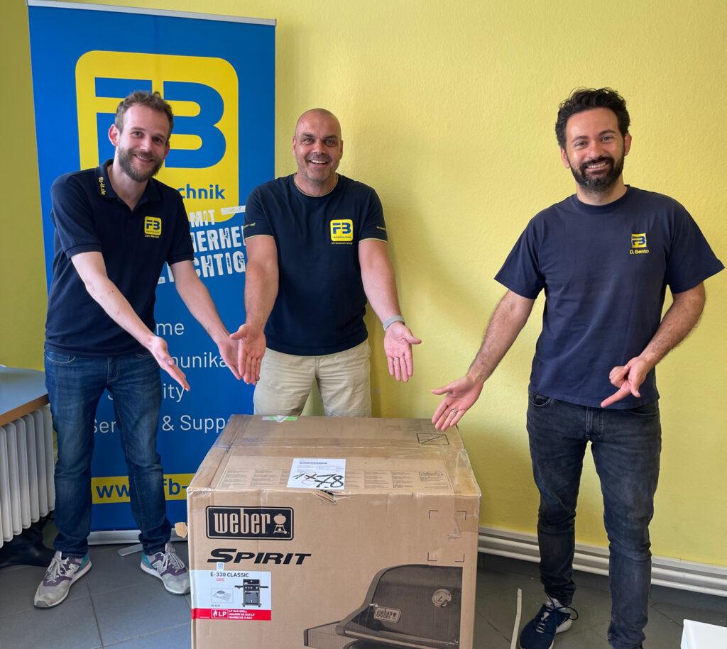 Systemfachinformatiker Jan Messe, Geschäftsführer Frank Barthel und Seniortechniker Daniel Bento (v.l.) freuen sich über den neuen Grill.